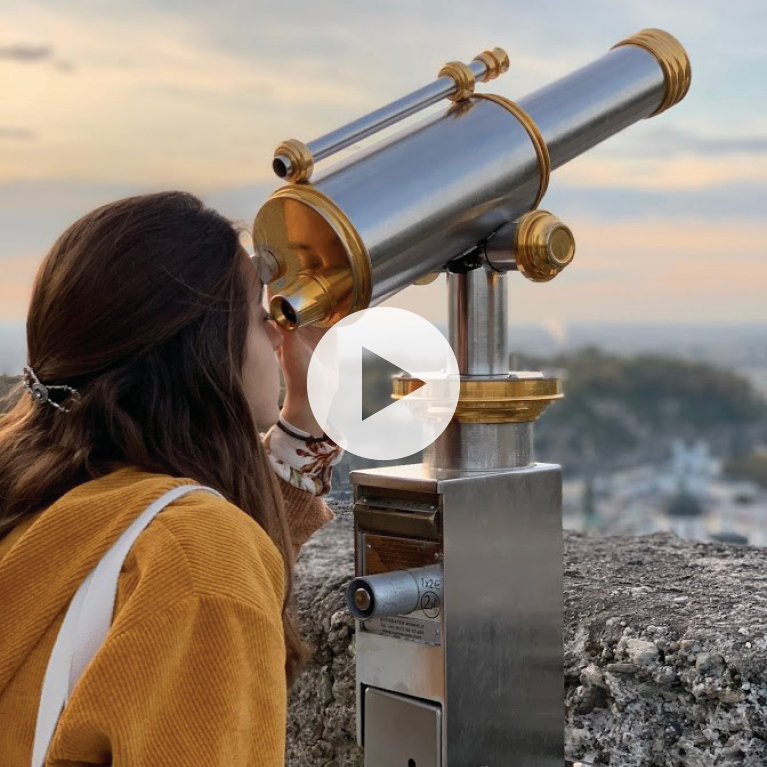 Female wearing yellow looking into a telescope
