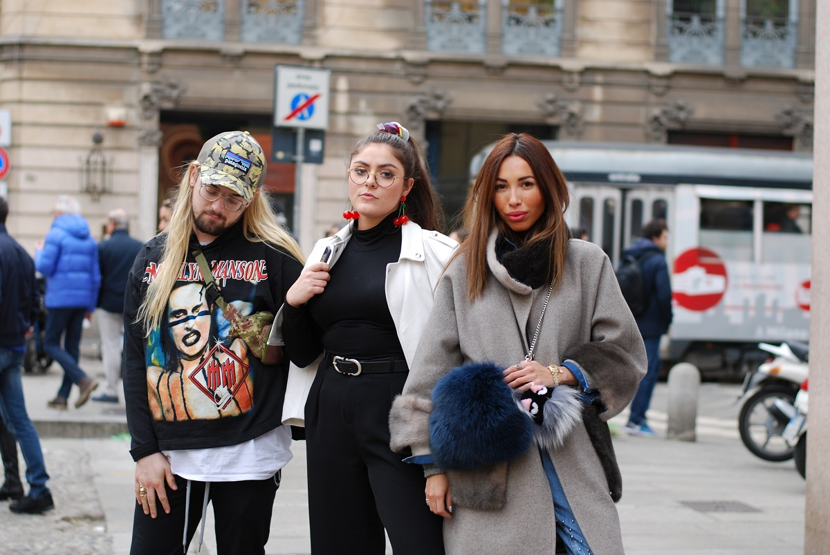 Three fashionable students post along street in Milan, Italy