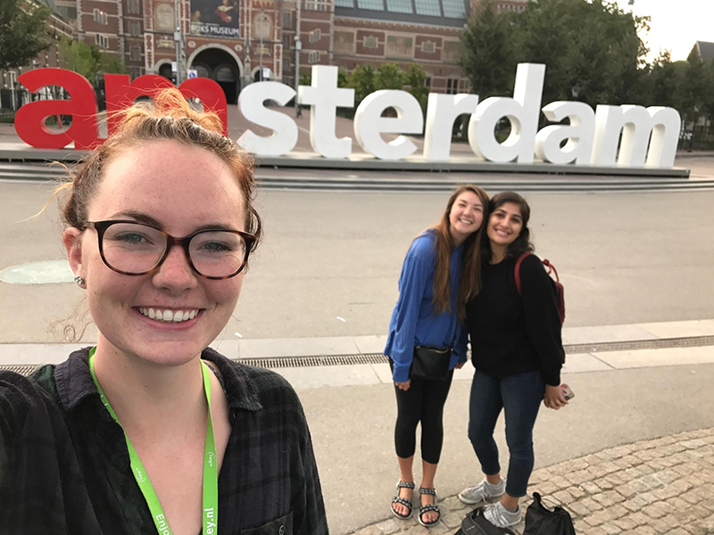 Students taking a selfie in front of the Amsterdam sign