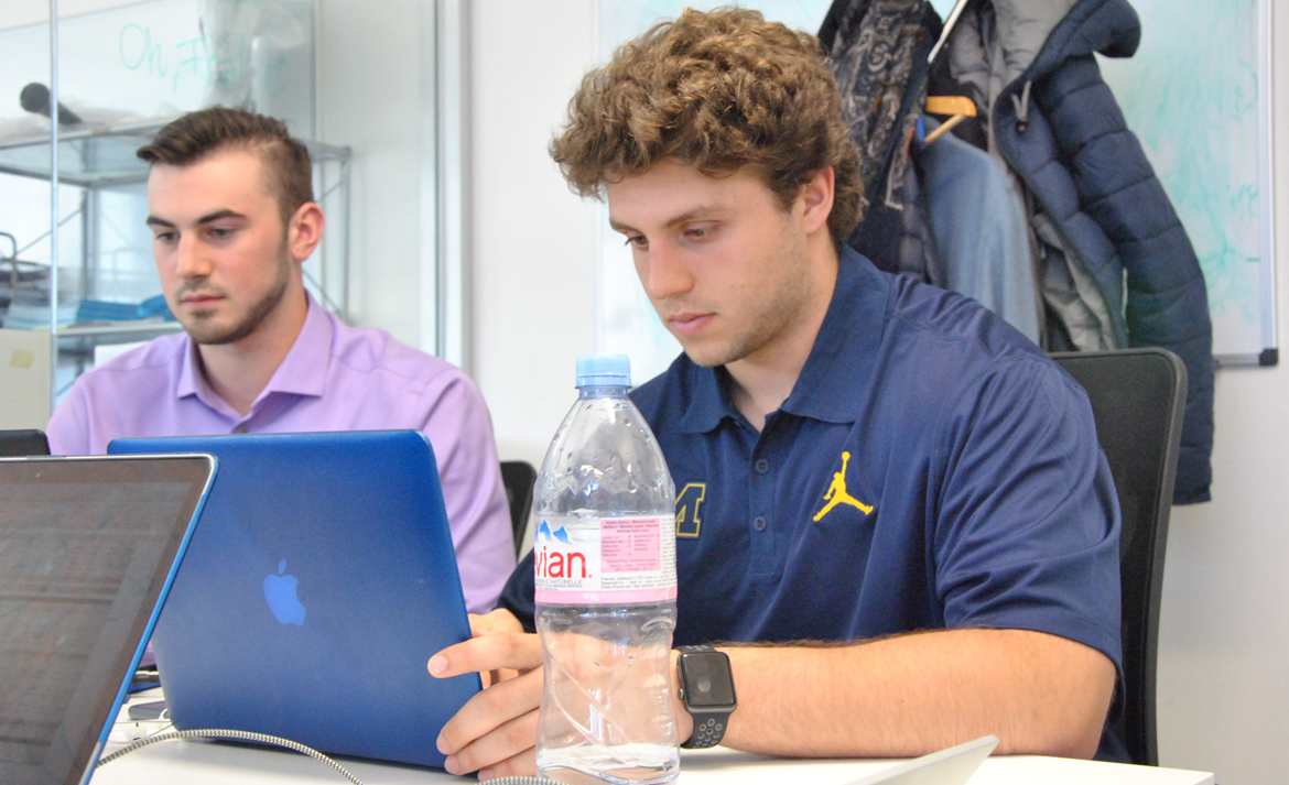 University of Michigan students working on laptops in office