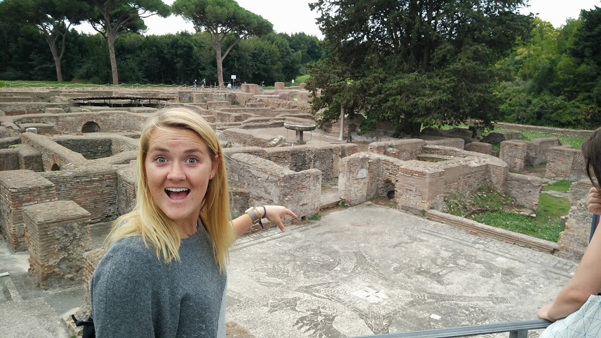 Student stands pointing at the Ostia Antica
