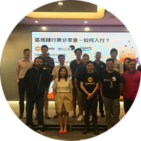 Intern in Hong Kong in front of large screen with Mandarin writing with group of colleagues