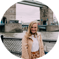 Intern in London in wearing khaki jacket in front of Tower Bridge