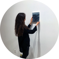 Intern in New York hanging a painting in a gallery