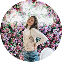 "Sydney intern in white top and jean skirt in front of floral wall with neon sign that says ""hello gorgeous"""