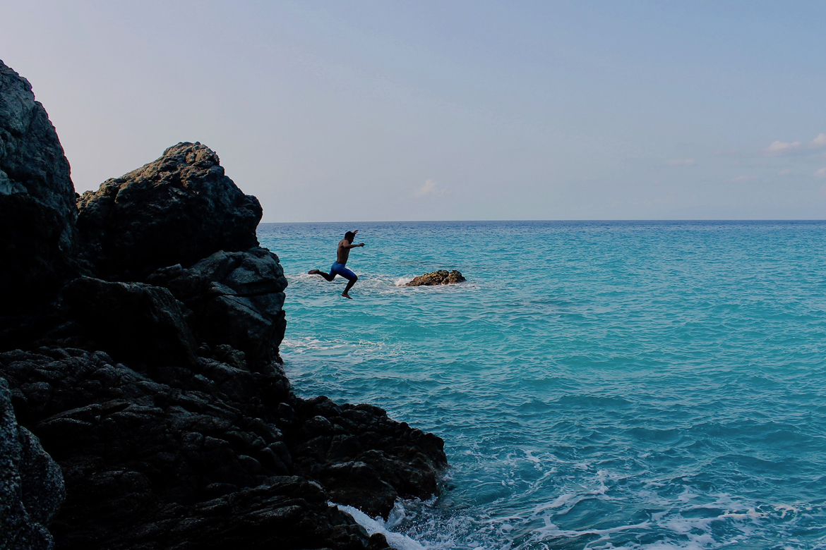 Student jumping off rocks into water in Italy