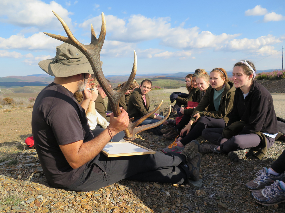 Guide holding antler talking with students