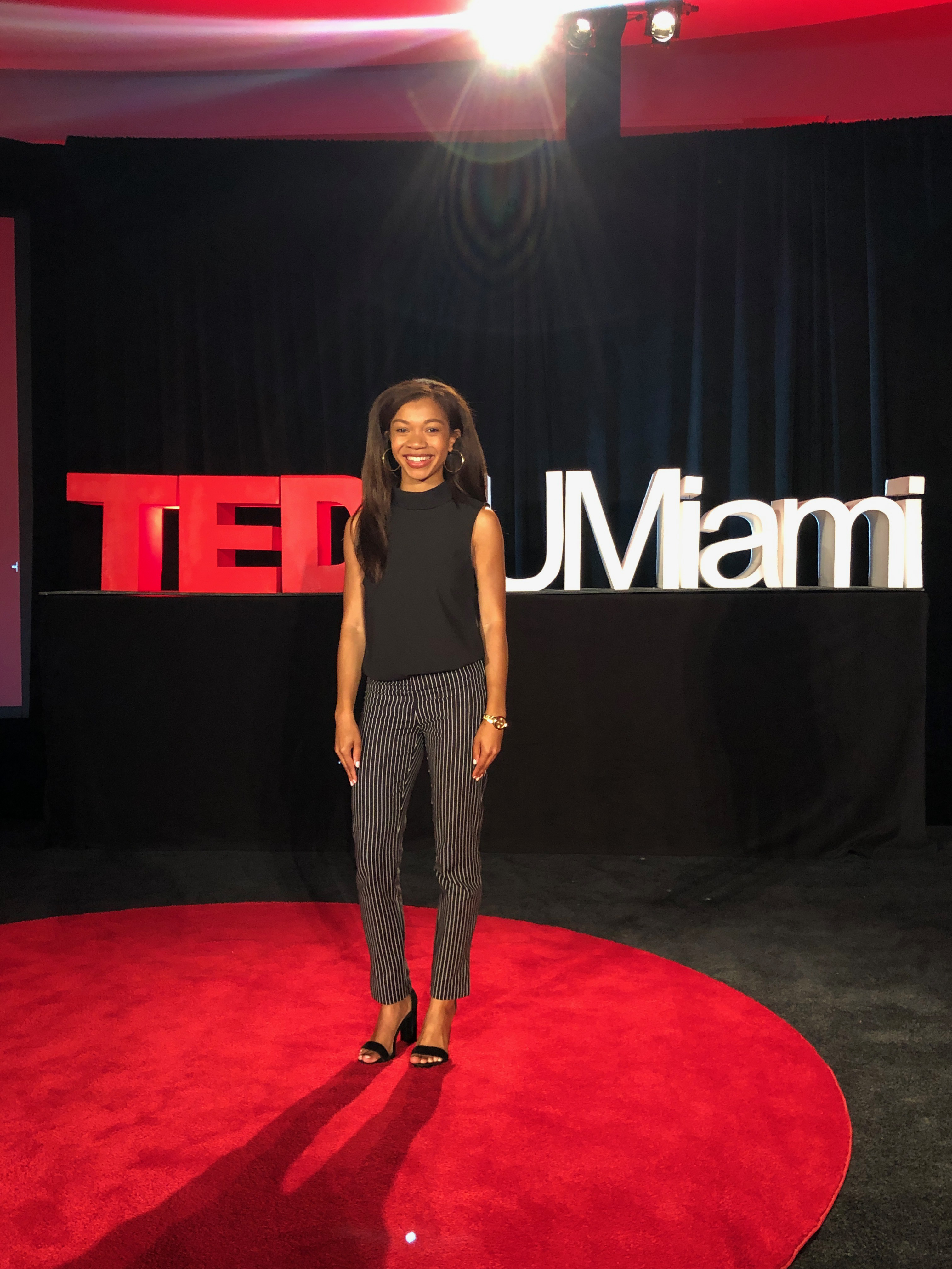 Breana Ross posing for a photo on stage for her TEDx talk.