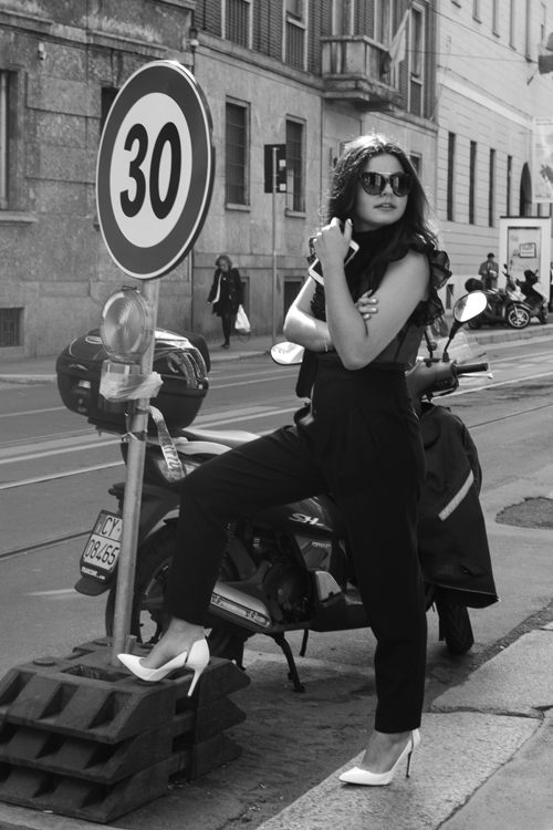 black and white photo of kathleen posing with a motorbike in Italy for her Front Row Tribe internship