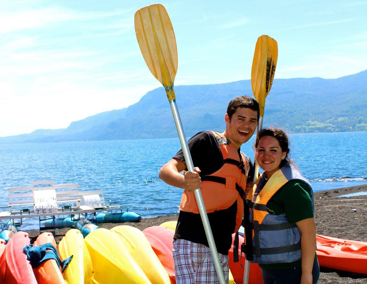 Justin and Monica pose in front of kayaks