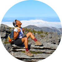 student laughing sitting on rock ledge in Cape Town, South Africa