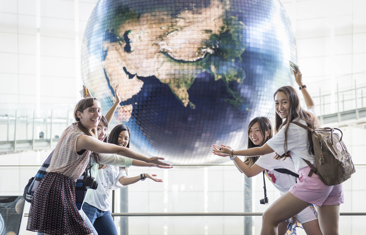 Tokyo students posing in front of large globe