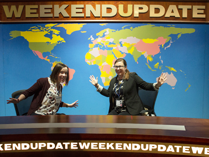 Attendees posing at the SNL Weekend Update set at the Museum of Broadcast Communications