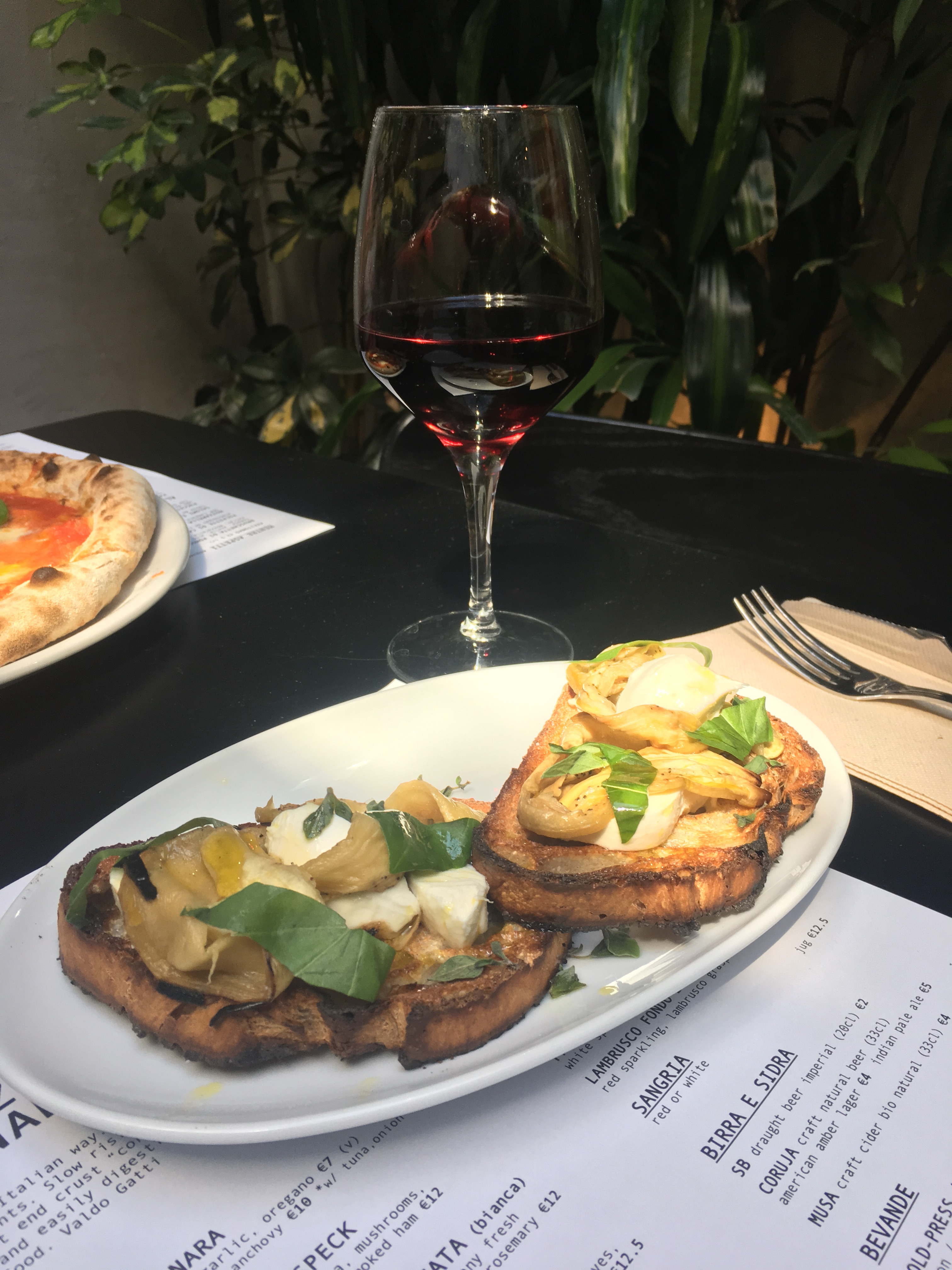 A plate of bruschetta and a glass of red wine