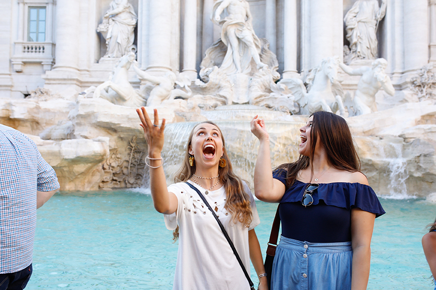 Students toss a coin into Trevi Fountain