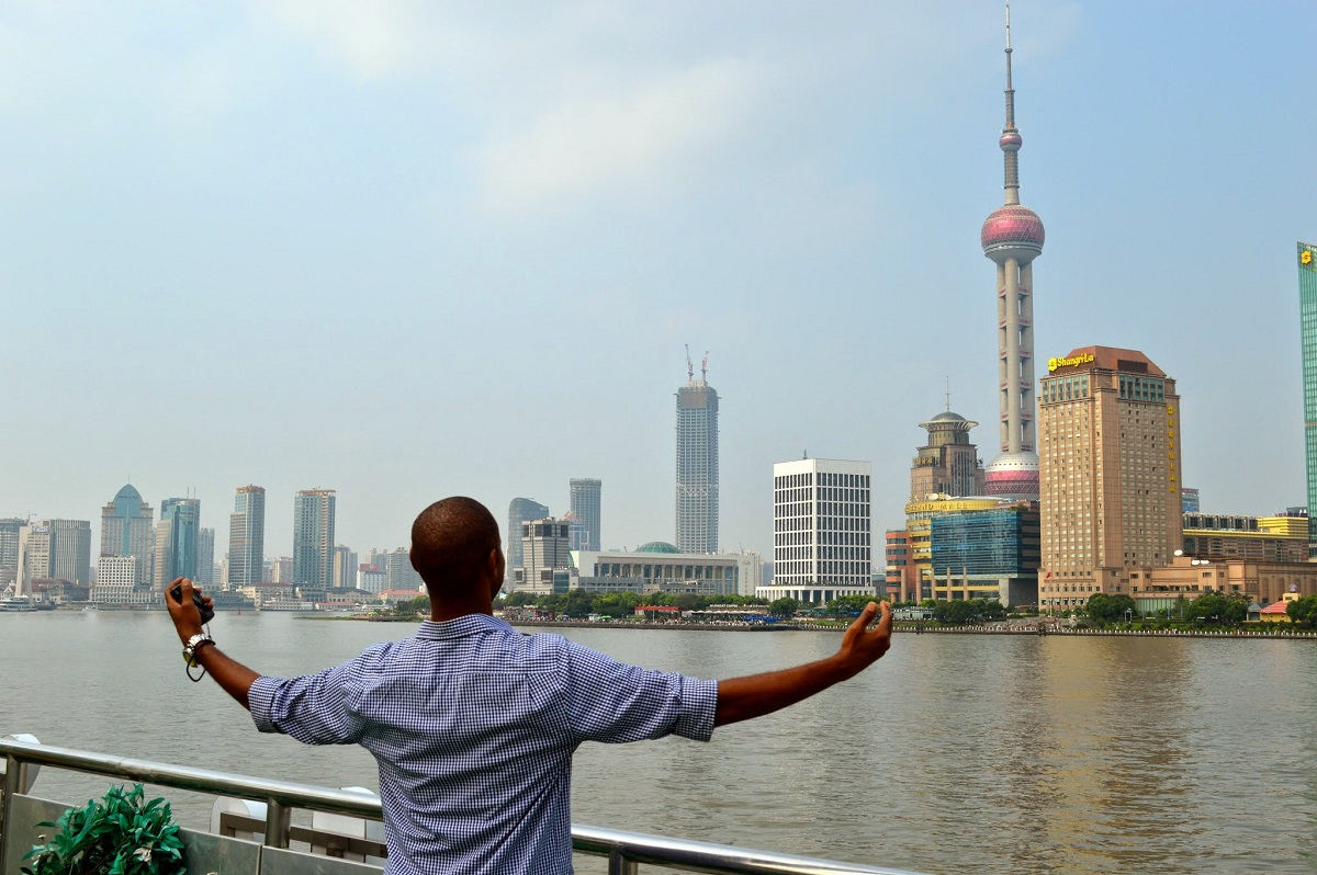 IES Abroad student power poses in front of Shanghai skyline