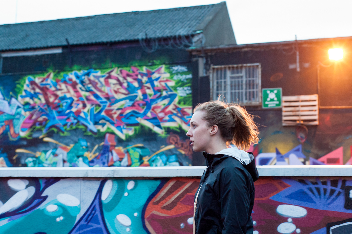 woman standing in front of building with graffiti in Dublin