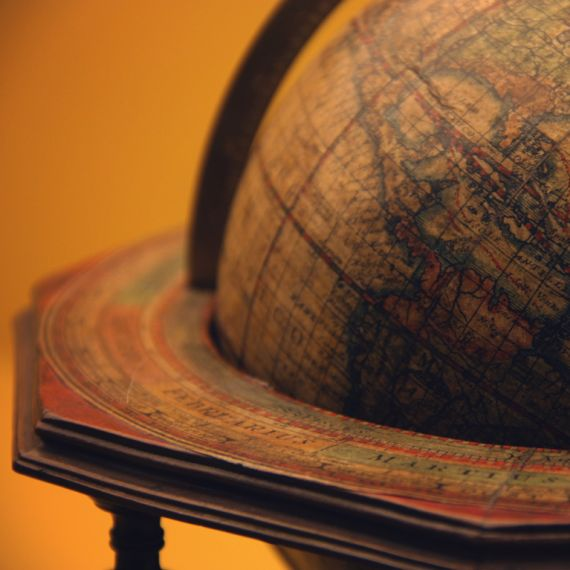 an old globe in a wooden holder