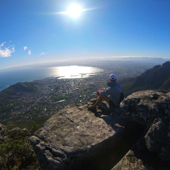 student sitting on a mountain overlooking Cape Town