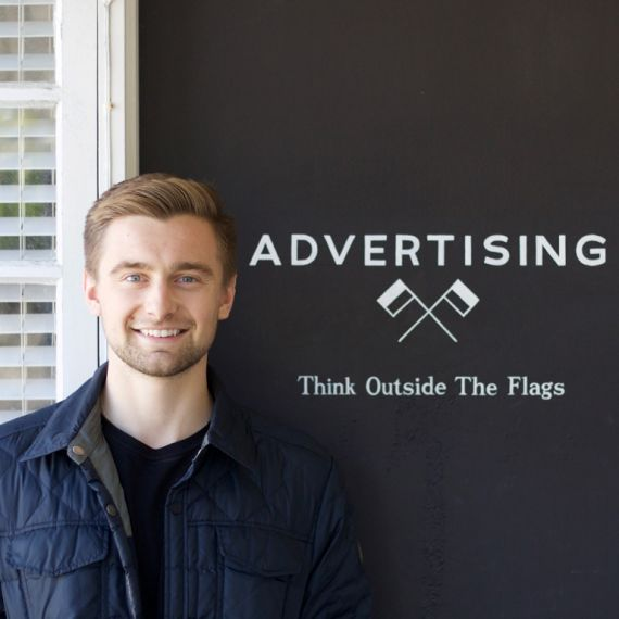 male intern smiling in front of a logo reading advertising and think outside the flags