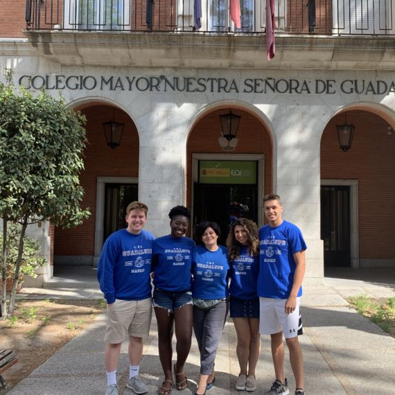 Diverse group Madrid students wearing matching t-shirts in front of university