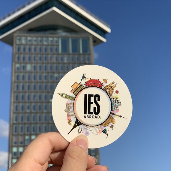 hand holding IES Abroad sticker in Amsterdam with tower in the background