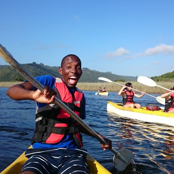 student in kayak wearing life jacket and smiling