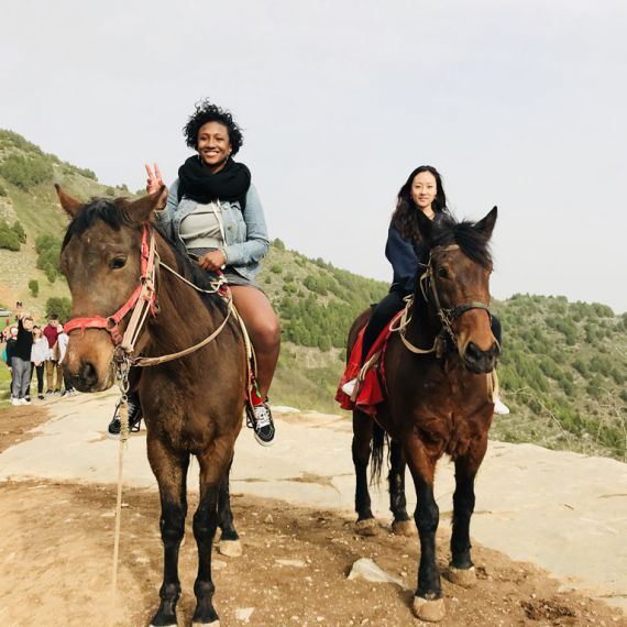 two study abroad students in China riding horses