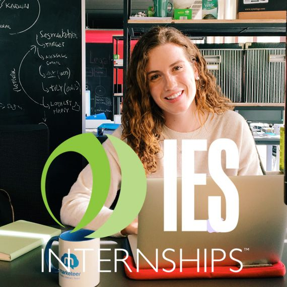 Intern in Barcelona at desk with IES Internships Logo overlay