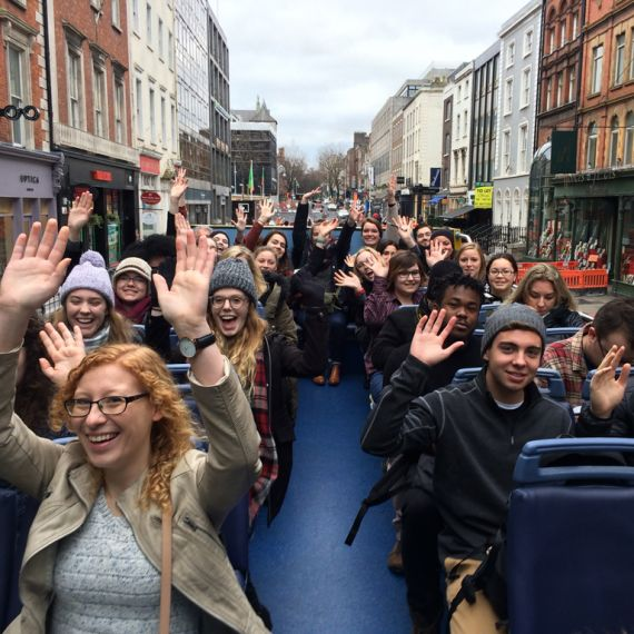 students on a tour bus in Dublin raising their hands