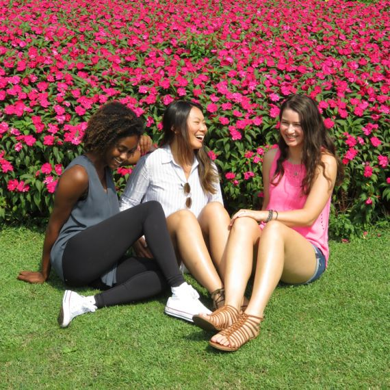 students laughing and sitting in garden with pink flowers