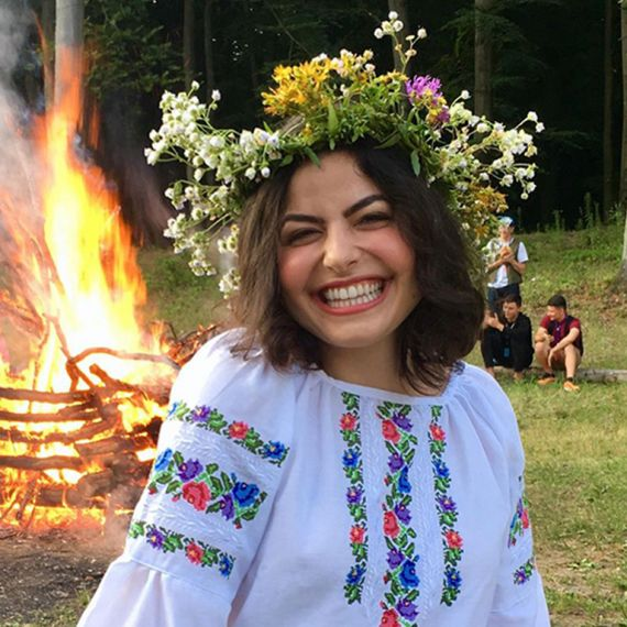 a woman wearing a flower crown and smiling in front of a bonfire