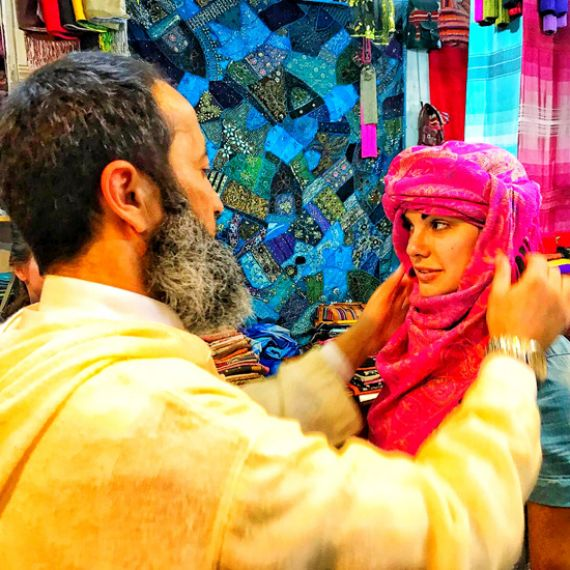 Moroccan local helping a student put on a traditional headwrap