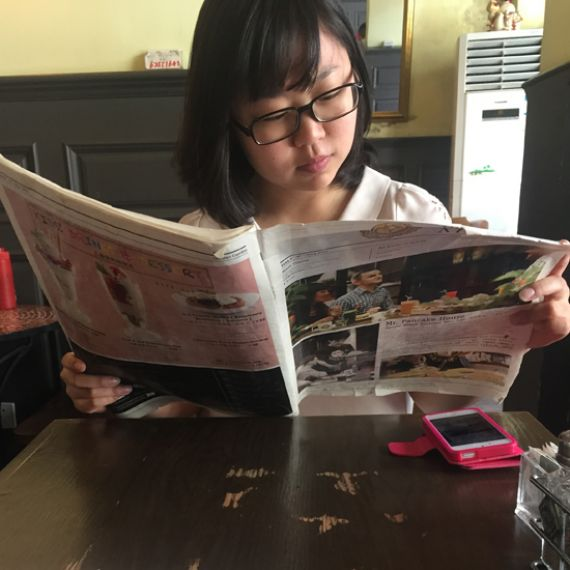 student reading a newspaper in China