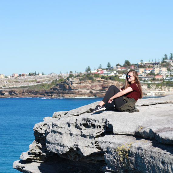 Sydney intern sitting on rocks near water