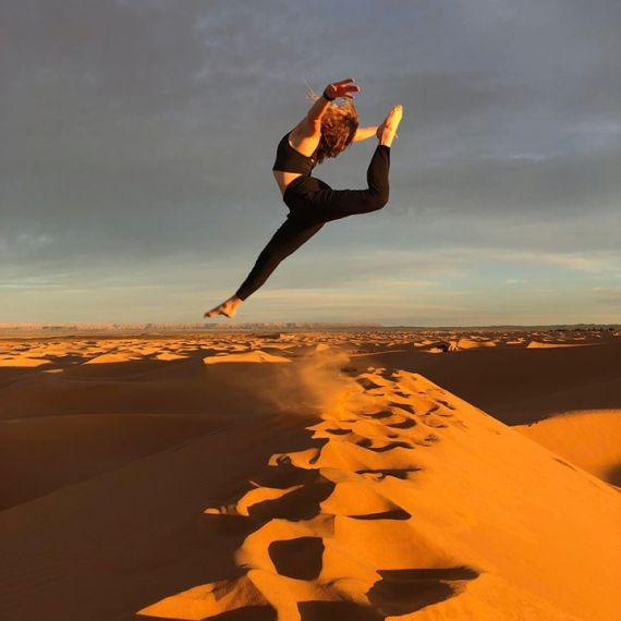Girl jumps over dune in Rabat