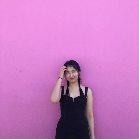 Mingjung Kwon in front of a bright pink wall in Los Angeles
