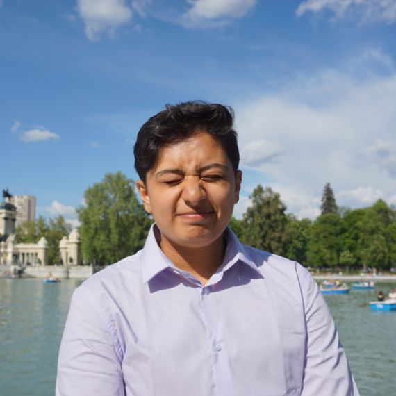 student standing in front of a body of water making a cringing face