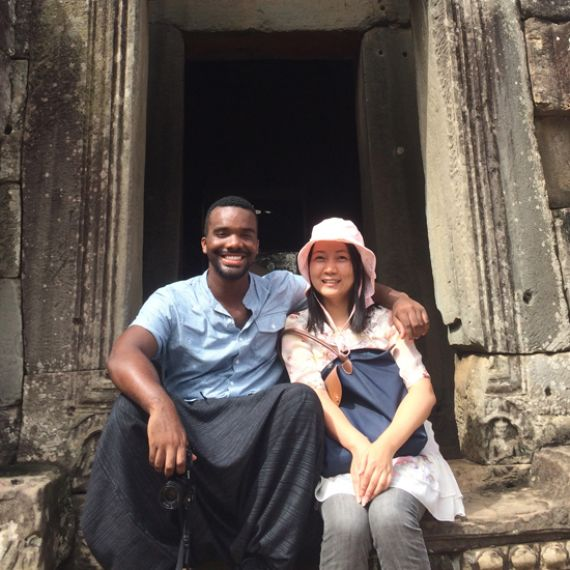 student sitting with local resident on steps of Chinese ruins