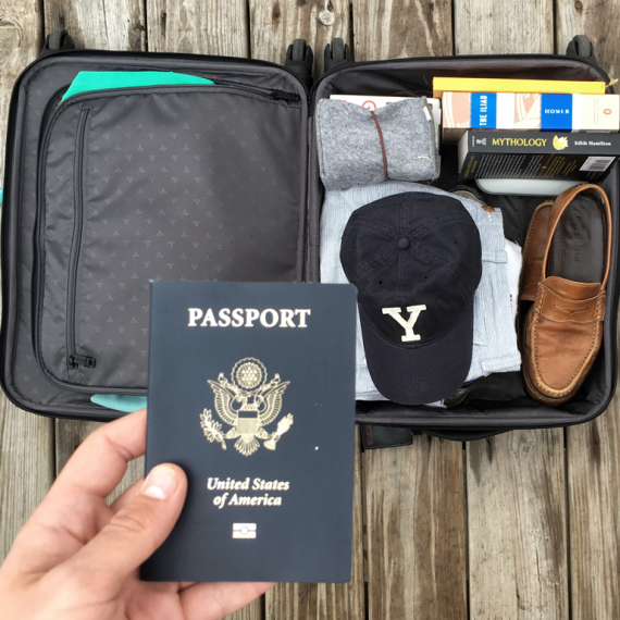 Hand holding a passport above suitcase with clothes and baseball cap in it