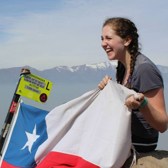 student with Chilean flag on mountain top
