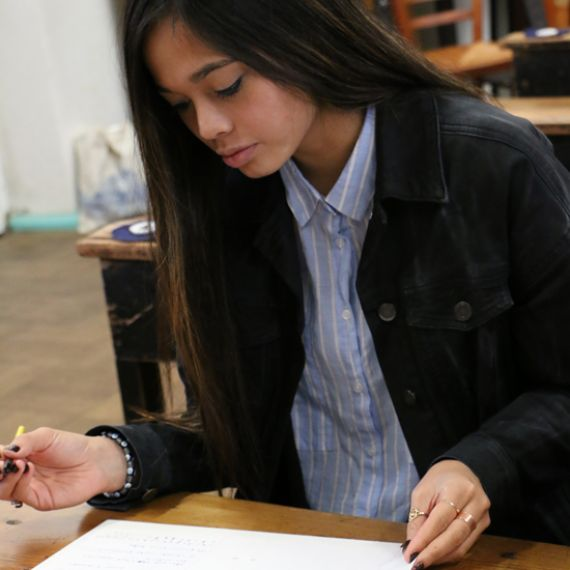 female student sitting at desk writing on a notebook