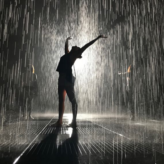student standing in rain room at Yuz Museum Shanghai with arms outstretched overhead