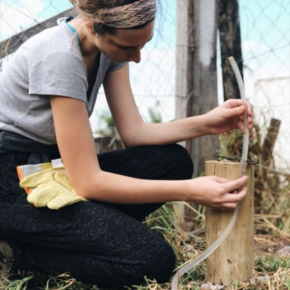 Idil tanrisever reparing a fence in Argentina