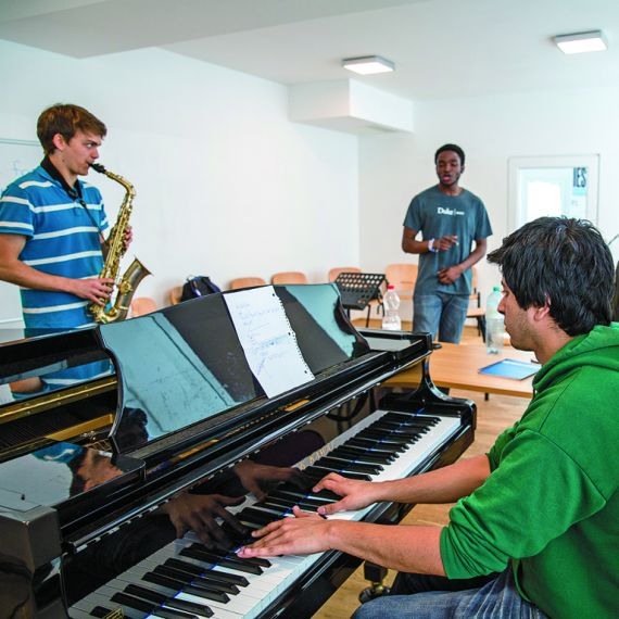 three music study abroad students rehearsing in IES Abroad Vienna music practice room