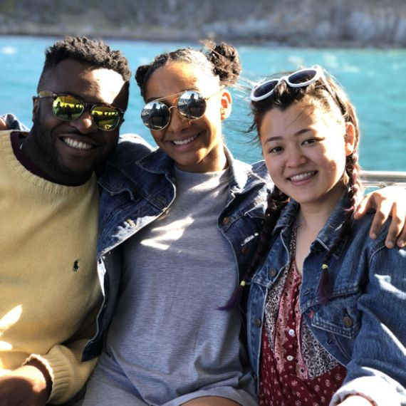three IES Abroad Cape Town students with sunglasses on a boat in South Africa