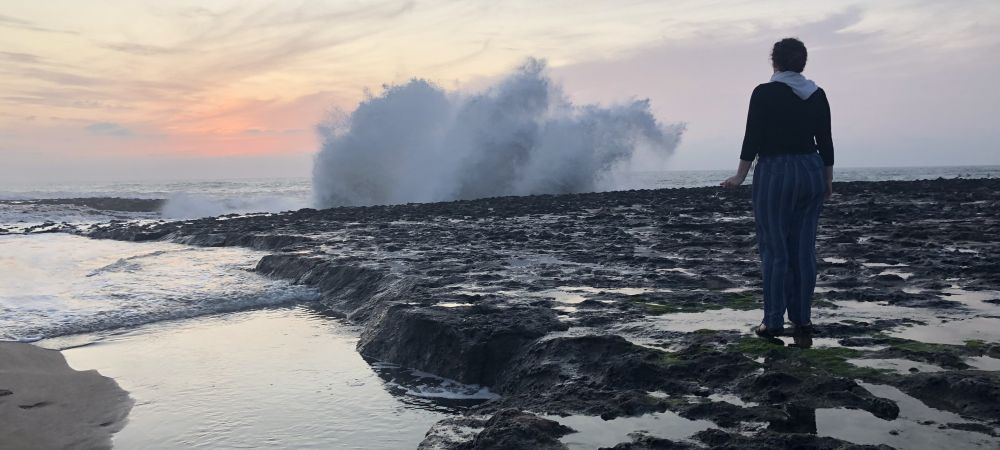 A person standing on a cliff looking at the sunset while a wave crashes up onto the cliff