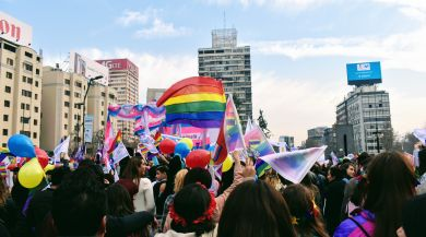 a group of people marching with rainbow flags