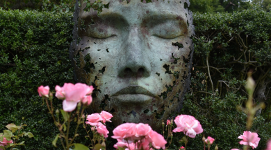 A sculpture of a face amongst the roses at Kew Gardens