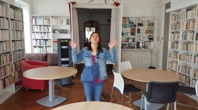 Girl standing in library with both hands palms up in a shrug, has a straight-faced expression